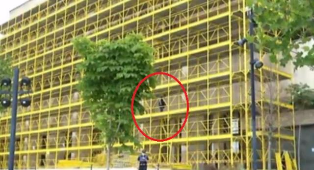 Një person ngjitet në një pallat në ndërtim,