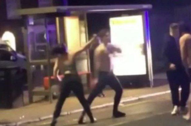 Dy burra zihen me grushte me një femër, gjysmë të zhveshur