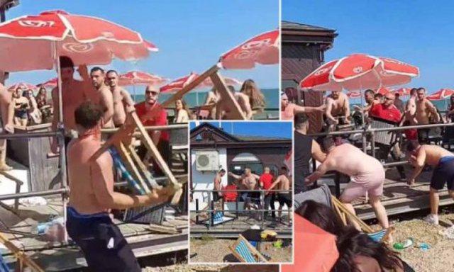 I bie dielli në kokë, burrat zihen me karrige në plazh